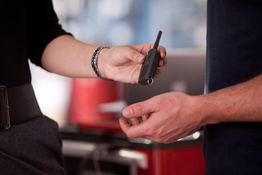 Woman Delivering Key to mechanic