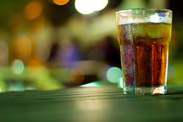 Glass full of drink by night, beautiful lights bokeh