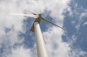 Fototapeta Wind turbine against a sky blue background with clouds obraz