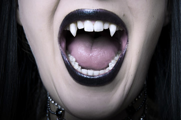 Opened vampire woman mouth closeup