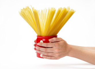 Woman's hands holding red jar with spaghetti inside