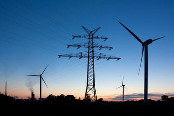 Strommast und Windräder bei Nacht