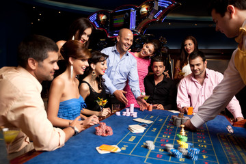 happy friends playing roulette in a casino