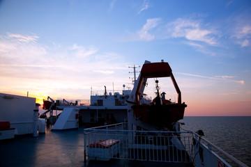 Ship deck view, ocean at sunset