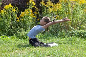 Девочка выполняет гимнастическое упражнение на природе.