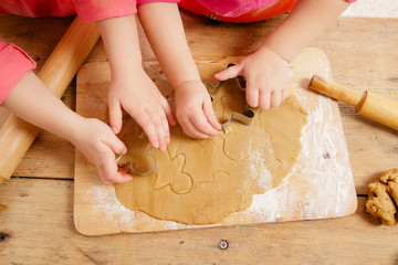 little girls cutting  gingerbread christmas cookies, hands only