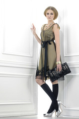fashion model holding little purse posing in the studio
