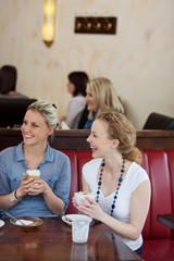 freundinnen lachen im café