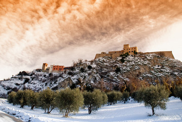 medieval village at sunset  with orange sky and snow