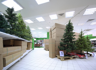 Shelves with variety of artificial Christmas tree inside store