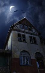 Sinister old house in Halloween night. Bats, Moon