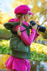 young girl taking photos in autumn park