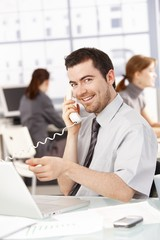 Happy businessman using laptop talking on phone
