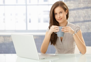 Portrait of smiling woman with computer