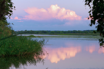 Colored clouds over the river at sunset