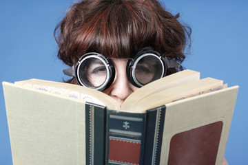 A cute woman wearing goggles with a book