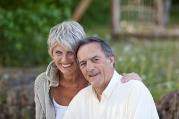 lachendes älteres paar sitzt draußen