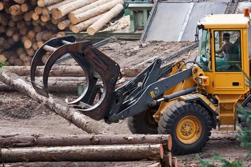 Skidder hauling logs at sawmill.