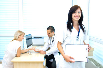 Young nurse, behind the doctor advises the patient