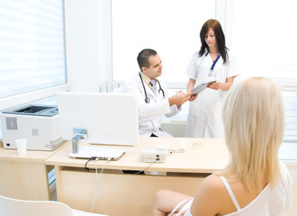 Nurse shows the folder to the doctor, the patient is waiting