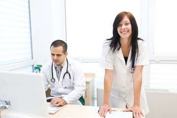 Happy nurse behind the doctor is working on a laptop