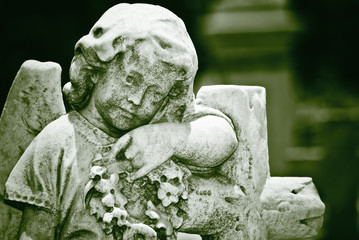Old statue of an infant angel  in green shades