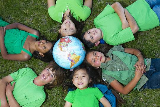 Children laying in grass around globe