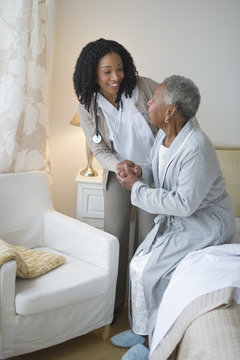 Nurse helping woman get out of bed