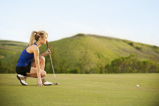 Caucasian woman checking ground on golf course