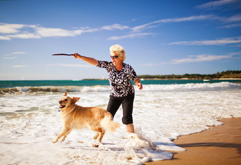 Woman playing on the beach with golden retriever