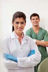 Happy female dentist smiling with arms crossed