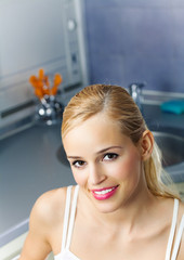 Portrait of smiling attractive woman, at kitchen