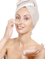 The beautiful young woman in towel with a cosmetic cream..