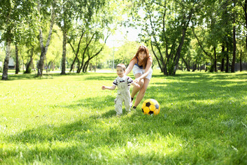 Little boy in the park playing with a ball