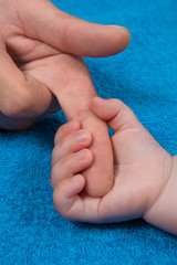 Baby is holding father's finger