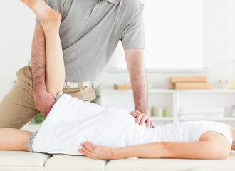 Chiropractor is stretching a woman's leg