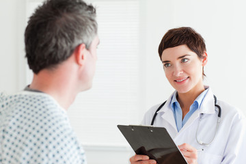 Doctor talking to a male patient holding a chart