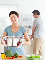 Charming wife holding a pot while her husband is washing the dis