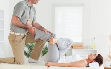 Chiropractor stretching woman's leg