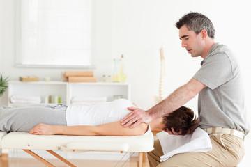 Masseur stretching a woman's head