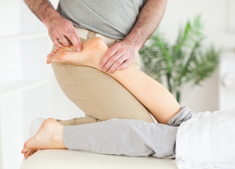 Masseur massaging a female customer's foot