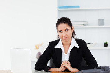 Serious businesswoman sitting at workplace