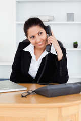 Smiling businesswoman telephoning