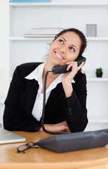 Cheerful cute businesswoman telephoning