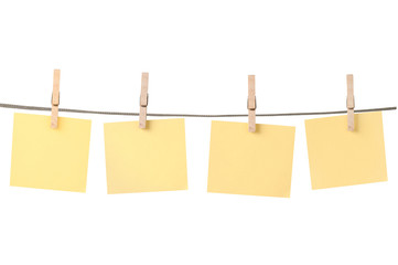 Blank pieces of paper and clothespins on white background