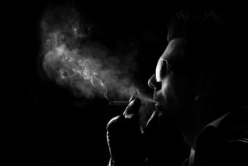 Man blows smoke on a dark