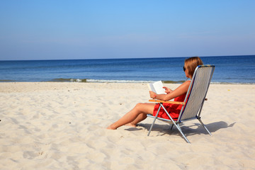 Young woman reading book on the sunny beach
