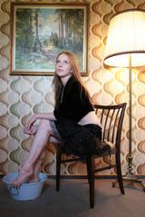 Frau nimmt Fußbad im Retro-Wohnzimmer