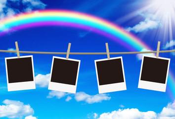 ロープに吊るされた無地の写真と虹の空