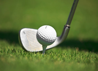 Golf ball and iron against the grass.